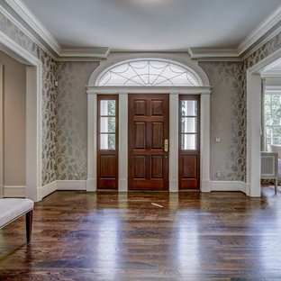 Réalisation d'un hall d'entrée tradition de taille moyenne avec un mur multicolore, un sol en bois foncé et un sol marron.