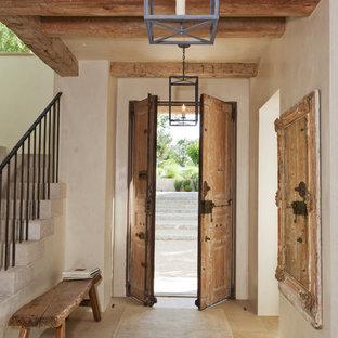 Design ideas for a mediterranean foyer in Austin with beige walls, a double front door, a medium wood front door and beige floors.