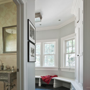 Ornate slate floor and black floor mudroom photo in New York with gray walls