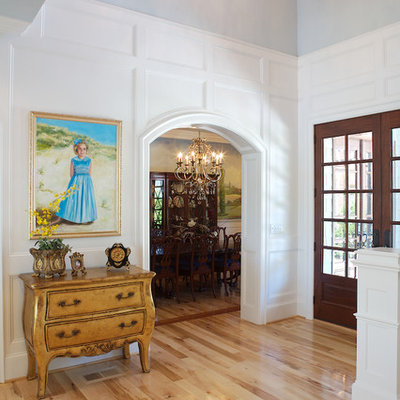 Inspiration for a timeless light wood floor foyer remodel in Charlotte with white walls