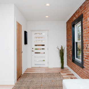 Urban light wood floor entryway photo in Denver with white walls and a white front door