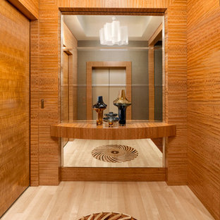 Example of a coastal light wood floor entry hall design in Miami with brown walls