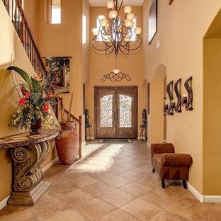 Idee per un grande corridoio mediterraneo con pareti arancioni, pavimento in travertino, una porta a due ante, una porta in legno bruno e pavimento beige
