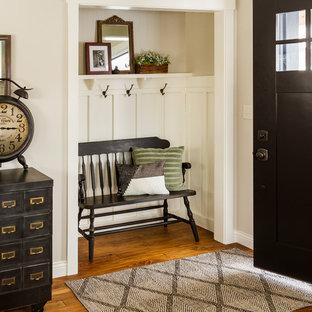Idéer för att renovera ett lantligt kapprum, med beige väggar, mellanmörkt trägolv, en enkeldörr och en svart dörr