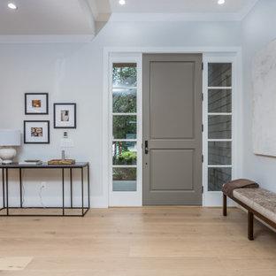 ロサンゼルスの巨大な片開きドアトランジショナルスタイルのおしゃれな玄関ロビー (白い壁、淡色無垢フローリング、グレーのドア、ベージュの床、折り上げ天井) の写真