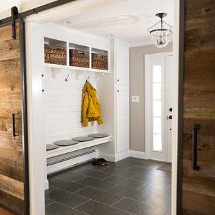 Exemple d'une entrée moderne de taille moyenne avec un vestiaire, un mur beige, un sol en carrelage de céramique, une porte simple et une porte blanche.