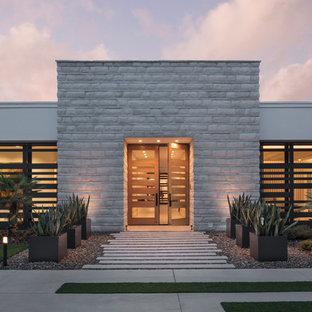 Immagine di una porta d'ingresso design con pareti bianche, pavimento in cemento, una porta a due ante, una porta in legno chiaro e pavimento grigio