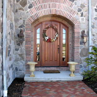 Example of a tuscan entryway design in New York with a medium wood front door