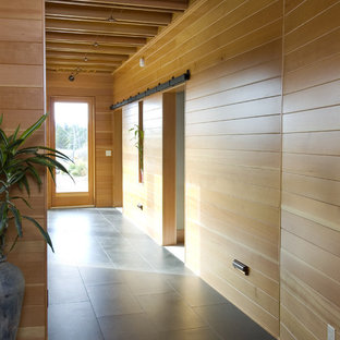 Example of a trendy entryway design in Seattle with beige walls and a glass front door