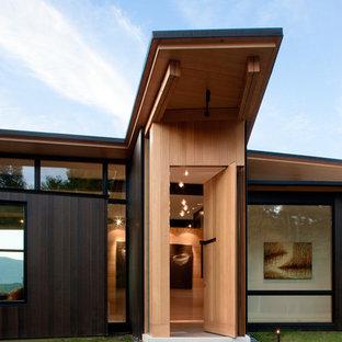 Bild på en funkis ingång och ytterdörr, med en pivotdörr, mellanmörk trädörr och beige väggar
