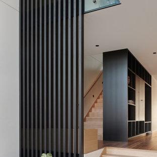 Imagen de distribuidor panelado, actual, de tamaño medio, panelado, con puerta pivotante, puerta marrón, panelado, paredes blancas, suelo de madera en tonos medios y suelo naranja