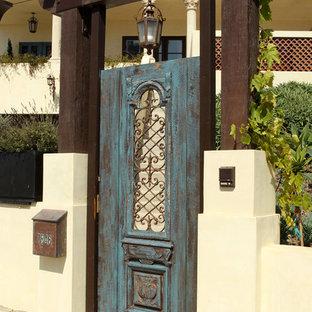 Großer Mediterraner Eingang mit Einzeltür, blauer Tür, beiger Wandfarbe, Betonboden und grauem Boden in Los Angeles