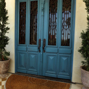 Large tuscan marble floor and multicolored floor entryway photo in Los Angeles with beige walls and a blue front door