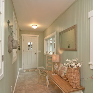 Example of a coastal porcelain floor and beige floor entryway design in Seattle with green walls and a white front door