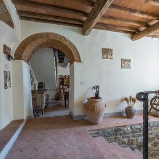 Свежая идея для дизайна: маленькая прихожая в стиле кантри с белыми стенами, полом из терракотовой плитки и входной дверью из светлого дерева - отличное фото интерьера