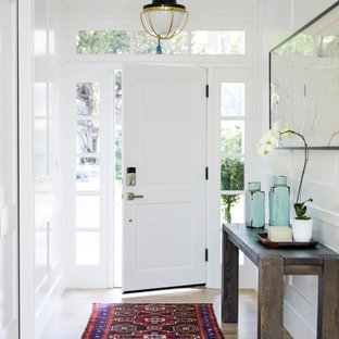 Inspiration for a mid-sized transitional light wood floor entryway remodel in San Francisco with white walls and a white front door