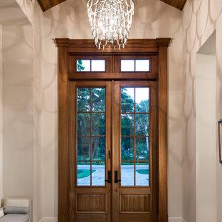 Réalisation d'une entrée chalet avec un mur blanc, un sol en bois foncé, une porte double, une porte en bois foncé et un sol marron.
