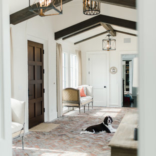 Mid-sized tuscan brick floor and red floor entryway photo in Jacksonville with white walls and a dark wood front door