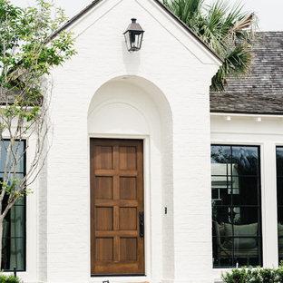 На фото: большая входная дверь в средиземноморском стиле с белыми стенами, кирпичным полом, одностворчатой входной дверью, входной дверью из дерева среднего тона и красным полом