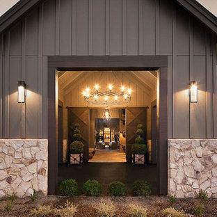 Modelo de vestíbulo de estilo de casa de campo, grande, con paredes beige, suelo de cemento, puerta corredera, puerta metalizada y suelo beige