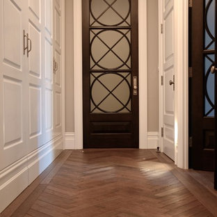 Entryway - mid-sized traditional dark wood floor and brown floor entryway idea in Other with white walls and a glass front door