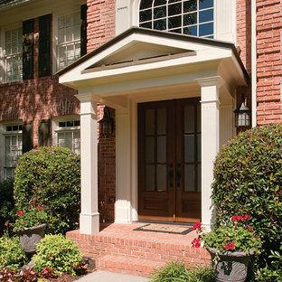 Idee per una porta d'ingresso chic di medie dimensioni con pavimento in mattoni, una porta a due ante e una porta in legno scuro