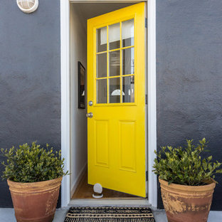 Inspiration for a transitional concrete floor and gray floor entryway remodel in San Francisco with gray walls and a yellow front door