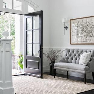 Idée de décoration pour un hall d'entrée tradition avec un mur blanc, un sol en bois foncé, une porte simple, une porte noire, un sol noir et boiseries.