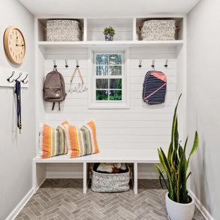 ローリーのビーチスタイルのおしゃれなマッドルーム (磁器タイルの床、グレーの床、白い壁、塗装板張りの壁) の写真