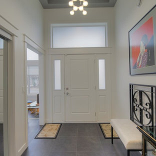 Mid-sized gray floor entryway photo with white walls and a white front door