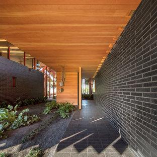 Entryway - mid-century modern entryway idea in Oklahoma City with a medium wood front door