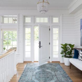 Bild på en mellanstor vintage foajé, med vita väggar, mellanmörkt trägolv, en enkeldörr, en vit dörr och brunt golv