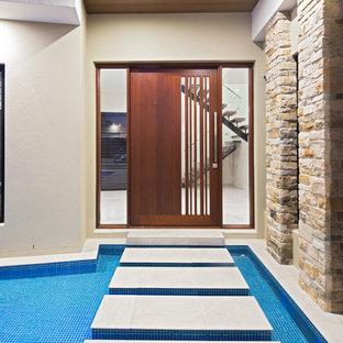 Contemporary front door in Brisbane with beige walls, a single front door and a dark wood front door.
