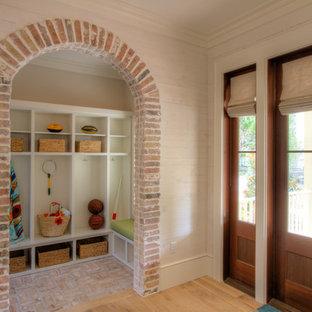 Diseño de vestíbulo posterior costero, grande, con suelo de ladrillo, paredes blancas, puerta simple y puerta de madera en tonos medios