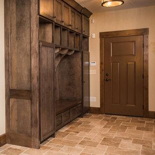 Foto di un ingresso con anticamera stile rurale di medie dimensioni con pareti beige, pavimento in travertino, una porta singola e una porta marrone