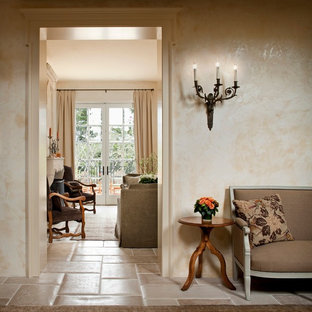 Entryway - mid-sized mediterranean travertine floor entryway idea in Other with beige walls and a white front door