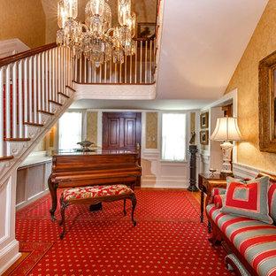 Idee per un grande ingresso tradizionale con pareti gialle, moquette, una porta singola, una porta in legno bruno e pavimento rosso