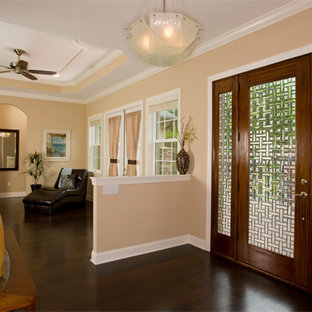 Inspiration for a mid-sized tropical dark wood floor entryway remodel in Tampa with beige walls and a glass front door