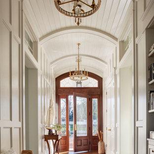 ボルチモアの片開きドアビーチスタイルのおしゃれな玄関 (白い壁、濃色無垢フローリング、ガラスドア、茶色い床、塗装板張りの天井、三角天井、パネル壁) の写真