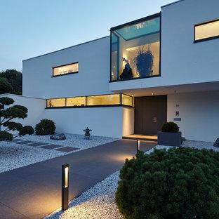 Mittelgroße Moderne Haustür mit weißer Wandfarbe, Betonboden, Drehtür, schwarzer Tür und grauem Boden in Köln