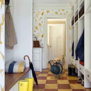 This is an example of a beach style entryway in Boston with white walls and multi-coloured floor.