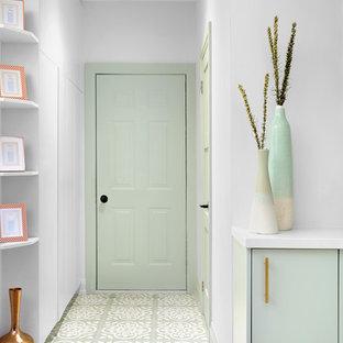 Inredning av en modern liten foajé, med vita väggar, betonggolv, en enkeldörr, en grön dörr och grönt golv