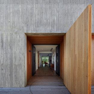 Inspiration for a midcentury front door in Los Angeles with grey walls, a double front door, a glass front door and grey floor.