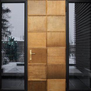 Пример оригинального дизайна интерьера: входная дверь в современном стиле с черными стенами, одностворчатой входной дверью, черным полом, гранитным полом и входной дверью из светлого дерева
