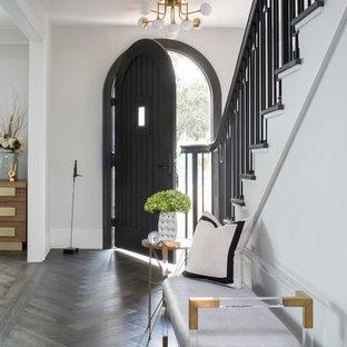 Идея дизайна: фойе среднего размера в стиле неоклассика (современная классика) с серыми стенами, паркетным полом среднего тона, одностворчатой входной дверью, коричневой входной дверью и коричневым полом