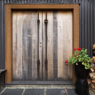 Foto di un ingresso o corridoio industriale con pareti nere, pavimento in ardesia, una porta a due ante e una porta in legno bruno