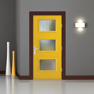 Immagine di una porta d'ingresso minimalista con pareti grigie, una porta singola e una porta gialla