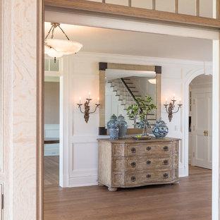 Ejemplo de distribuidor costero con paredes blancas y suelo de madera en tonos medios