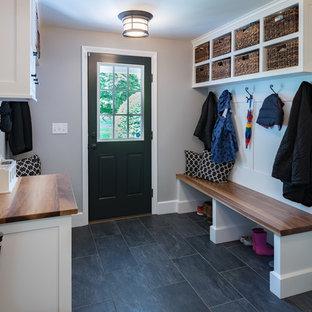 ボストンの片開きドアエクレクティックスタイルのおしゃれなマッドルーム (グレーの壁、スレートの床、黒いドア、グレーの床) の写真