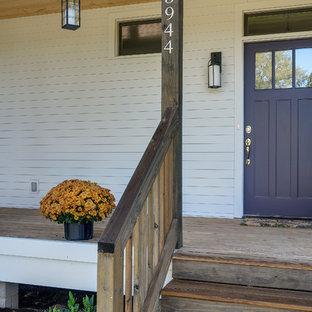 Foto på en stor lantlig ingång och ytterdörr, med vita väggar, en enkeldörr och en lila dörr